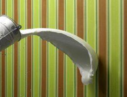 pared con papel tapiz recibiendo una cubeta de pintura