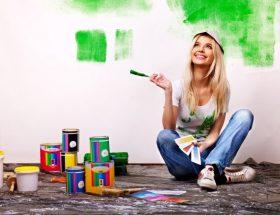 chica pintando su casa