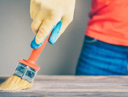 persona pintando madera con brocha